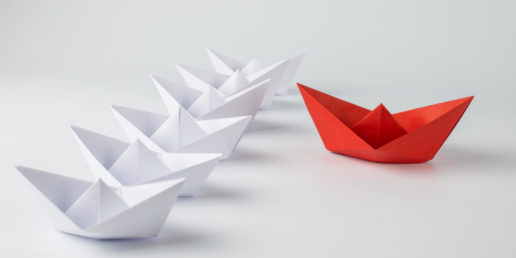 Image of 5 white paper boats and 1 red paper boat